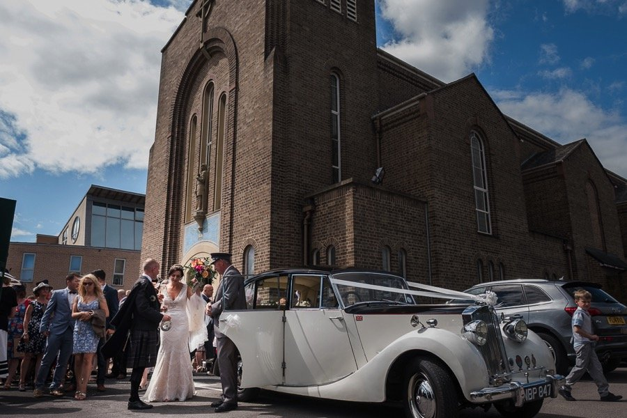Bride and groom and wedding car outside church