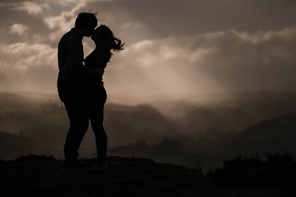 A Couple kiss at Curbar Edge in the Derbyshire Peak District