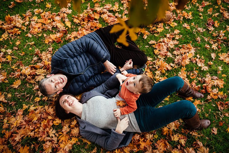 Family sitting in Autumn Leaves