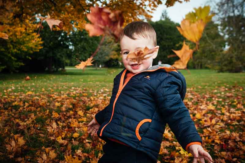 Little boy plays in leaves